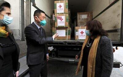 السفير الصيني جو وي (يسار) يتحدث مع وزيرة الصحة الفلسطينية مي الكيلة أثناء تفريغ شحنة من لقاحات سينوفارم المضادة لكوفيد-19 التي تبرعت بها الحكومة الصينية في مدينة رام الله بالضفة الغربية، في 29 مارس، 2021. (ABBAS MOMANI/AFP)