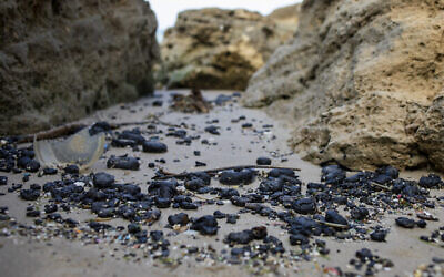 قطع من القطران التي انجرفت إلى الشاطئ جراء تسرب نفطي في البحر الأبيض المتوسط على شاطئ محمية غادور الطبيعية بالقرب من محمورت، إسرائيل، 1 مارس 2021. (AP Photo / Ariel Schalit)