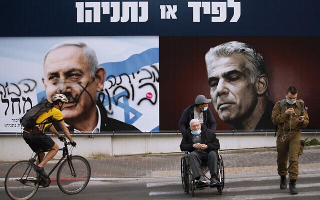 لوحة إعلانية لحملة حزب الليكود الانتخابية تظهر صورة زعيمه رئيس الوزراء بنيامين نتنياهو وزعيم حزب المعارضة يائير لبيد، في رمات غان، 21 مارس 2021 (AP Photo / Oded Balilty)