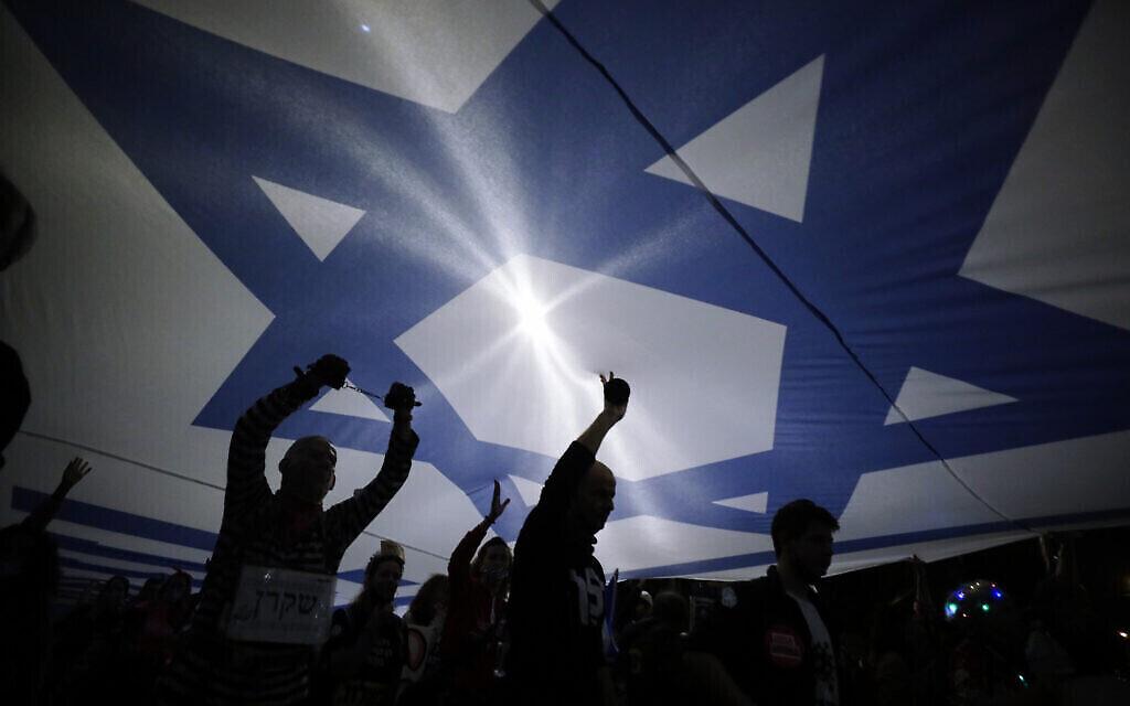 علم إسرائيلي كبير تم رفعه خلال مظاهرة ضد رئيس الوزراء بنيامين نتنياهو في القدس،  20 مارس، 2021. (AP Photo/Sebastian Scheiner)