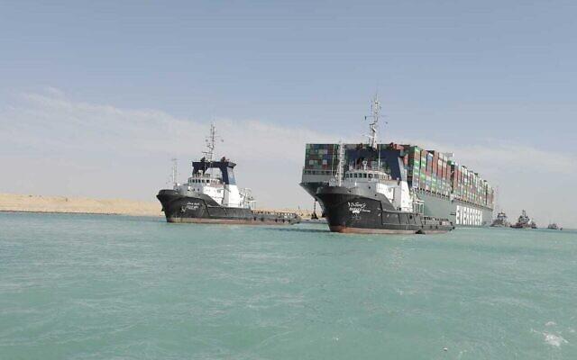 """قاطرات ترافق سفينة الشحن """"إيفر جيفن""""، التي ترفع علم بنما، أثناء تحركها في قناة السويس، مصر، 29 مارس 2021 (Suez Canal Authority via AP)"""