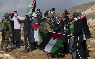 جنود إسرائيليون يمنعون متظاهرين فلسطينيين من الوصول إلى بؤرة استيطانية يهودية في أطراف قرية المغير بالضفة الغربية، شمال رام الله، 18 ديسمبر، 2020. (AP / Nasser Nasser)