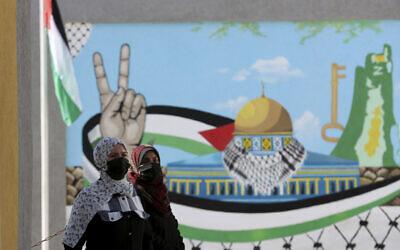 نساء يرتدين أقنعة الوجه أثناء انتظارهن في محطة التسجيل في لجنة الانتخابات المركزية لتسجيل أسمائهن في السجل الانتخابي في مدينة غزة، 10 فبراير 2021 (Adel Hana/AP)