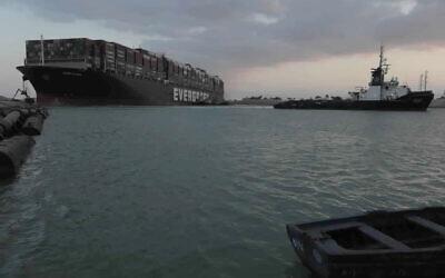 """قاطرات تعمل على تحرير سفينة """"إيفر جيفين"""" التي ترفع علم بنما والعالقة في قناة السويس، 28 مارس 2021 (Suez Canal Authority via AP)"""