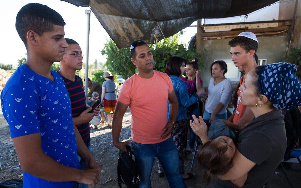 يهود اسرائيليون وفلسطينيون يتبادلون أطراف الحديثخلال لقاء اسبوعي نظمه علي ابو عواد، فلسطيني من الضفة الغربية، 22 يوليو، 2015. (Nati Shohat / Flash90)
