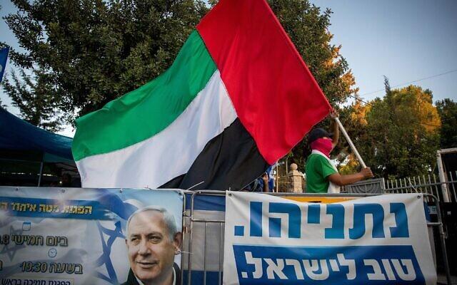 رجل يلوح بعلم كبير لدولة الامارات العربية المتحدة خارج منزل رئيس الوزراء في القدس، 19 اغسطس 2020 (Yonatan Sindel / Flash90)