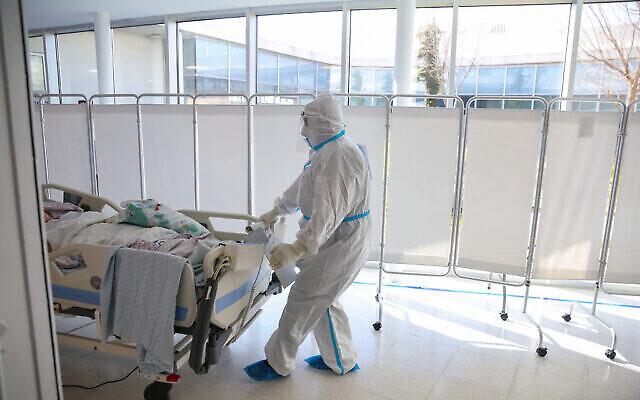 أحد أفراد الطاقم الطبي في مستشفى ينقل مريضا جديدا الى قسم الكورونا في المركز الطبي زيف في مدينة صفد شمال اسرائيل، 7 يناير، 2020. (David Cohen / Flash90)
