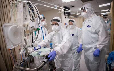 أعضاء فريق طبي في مستشفى شعاري تسيدك بزي واق خلال عملهم في قسم كورونا بالقدس، 19 يناير، 2021. (Yonatan Sindel/Flash90)