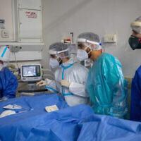 طاقم طبي في مستشفى هداسا عين كارم يرتدي الزي الواقي خلال عمله في قسم كورونا، 1 فبراير، 2021. (Olivier Fitoussi/Flash90)