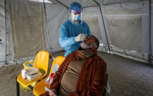 عامل صحي يأخذ عينة لفحص فيروس كورونا في مركز صحي في رفح، جنوب قطاع غزة، 16 فبراير 2021 (Abed Rahim Khatib / Flash90)