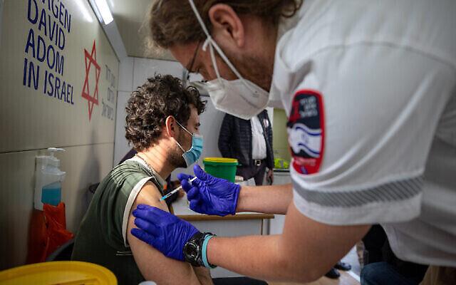 رجل إسرائيلي يتلقى جرعة لقاح كوفيد-19 في محطة تطعيم متنقلة لنجمة داود الحمراء في سوق محانيه يهودا في القدس، 22 فبراير، 2021. (Olivier Fitoussi / Flash90)