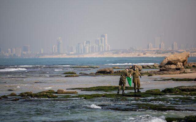 جنود ينظفون القطران قبالة شاطئ بالماخيم، بعد تسرب نفطي في البحر لوث معظم الساحل الإسرائيلي، 22 فبراير 2021 (Yonatan Sindel / Flash90)