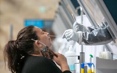 يجمع عينات مسحة من الأنف في محطة لاختبارات كورونا في مطار بن غوريون الدولي، 28 فبراير، 2021. (Yossi Aloni / Flash90)