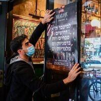 عامل يضع ملصقا إعلانيا للبحث عن عاملين في مطعم في تل أبيب، 3 مارس، 2021. (Avshalom Sassoni / Flash90)