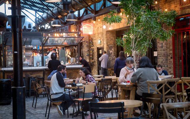 أشخاص يستمتعون بتناول الطعام في المطاعم بعد إعادة افتتاحها مؤخرًا في تل أبيب، 7 مارس 2021 (Miriam Alster / Flash90)