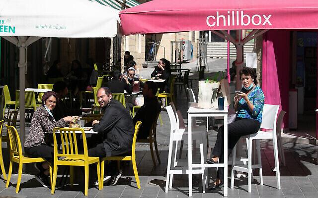 زبائن يجلسون في مقهى في القدس بعد إعادة فتحه بعد تخفيف قيود فيروس كورونا، 7 مارس، 2021. (Olivier Fitoussi / Flash90)