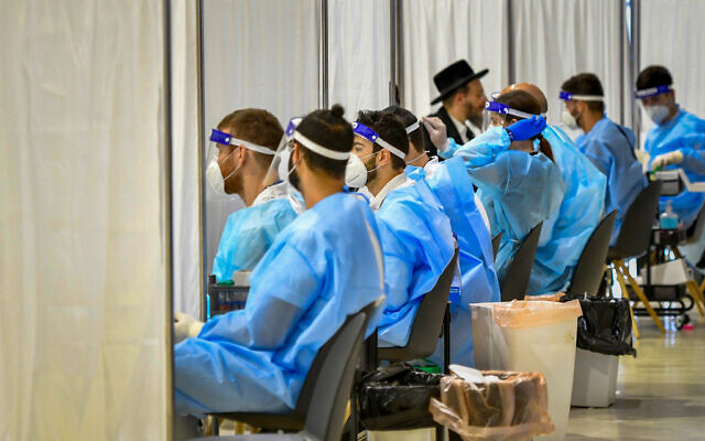 عمال طبيون يختبرون ركاب لكوفيد-19 في مطار بن غوريون الدولي، 8 مارس 2021 (Avshalom Sassoni / Flash90)