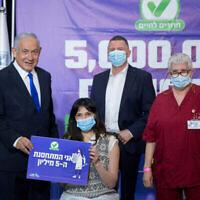 رئيس الوزراء بنيامين نتنياهو (يسار) ووزير الصحة يولي إدلشتين (الثاني من اليمين) خلال زيارة إلى مركز تطعيم ضد كوفيد-19 تابع لصندوق المرضى لئوميت في تل أبيب، مع المتطعمة الإسرائيلية رقم 5 مليون، 8 مارس، 2021. (Miriam Alster / Flash90)