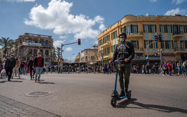 إسرائيليون يرتدون أقنعة وجه في تل أبيب، 12 مارس 2021 (Yahav Gamliel / Flash90)