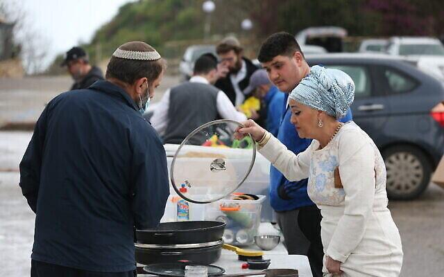 حريديم  يقومون بغسل أواني الطهي لإزالة أي آثار للخمير استعدادا لعيد الفصح  اليهودي في صفد، 25 مارس، 2021. (David Cohen/Flash90)