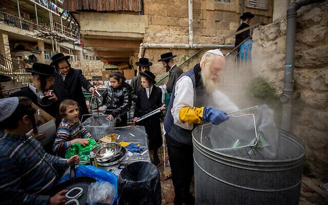 حريديم  يقومون بغسل أواني الطهي لإزالة أي آثار للخمير استعدادا لعيد الفصح  اليهودي  في حي مئة شعاريم بالقدس، 26 مارس، 2021. (Yonatan Sindel/Flash90)