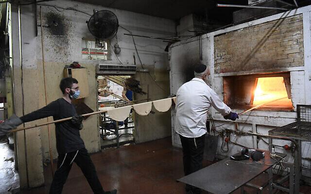 يهود حريديم يحضرون خبز المصة، ، وهو خبز تقليدي غير مختمر يؤكل خلال عيد الفصح اليهودي، في كفر حاباد، 25 مارس، 2021. (Yossi Zeliger / Flash90)