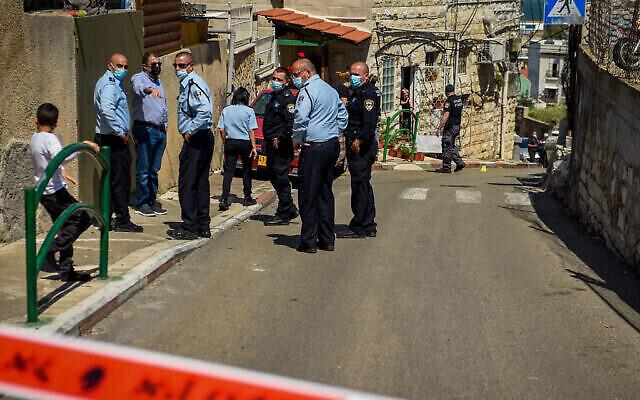 قوات الأمن تتفقد الموقع الذي قُتل رجل برصاص شرطي بعد أن حاول الرجل، كما يُزعم، طعن الشرطي، في حيفا، 29 مارس، 2021.(Roni Ofer/Flash90)