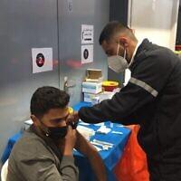أحمد عطوان، فلسطيني من بلدة قريبة من الخليل، يتلقى الجرعة الأولى من لقاح فيروس كورونا خلال حملة إسرائيلية لتطعيم الفلسطينيين العاملين في إسرائيل. (Aaron Boxerman/The Times of Israel)