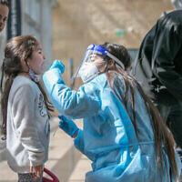 عاملة مختبر تجمع عينات مسحة من الأنف لاختبار كوفيد-19 في مطار بن غوريون الدول، 28 فبراير، 2021. (Yossi Aloni / Flash90)