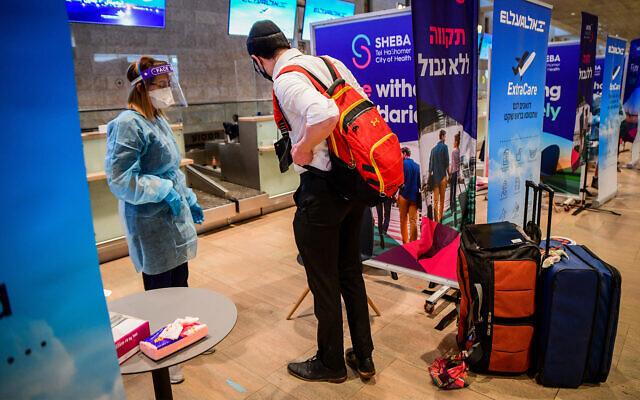 عاملون طبيون يجرون فحوصات كورونا لمسافرين في مطار بن غوريون الدولي، 8 مارس 2021 (Avshalom Sassoni / Flash90)