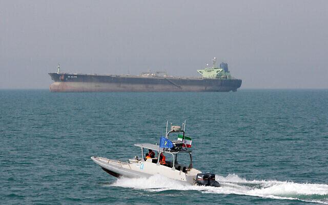 توضيحية: زورق سريع تابع للحرس الثوري الإيراني يتحرك في الخليج الفارسي وفي الخلفية تظهر ناقلة نفط، 2 يوليو، 2012. (AP Photo / Vahid Salemi، File)