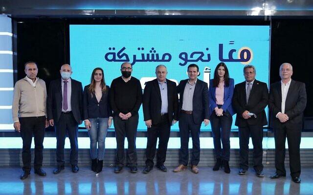 """زعيم حزب """"معا"""" أحمد دراوشة يقف وسط مجموعة من سياسيي """"القائمة المشتركة"""" أمام شعار يعلن وحدة الأحزاب (Courtesy: Ma'an)"""