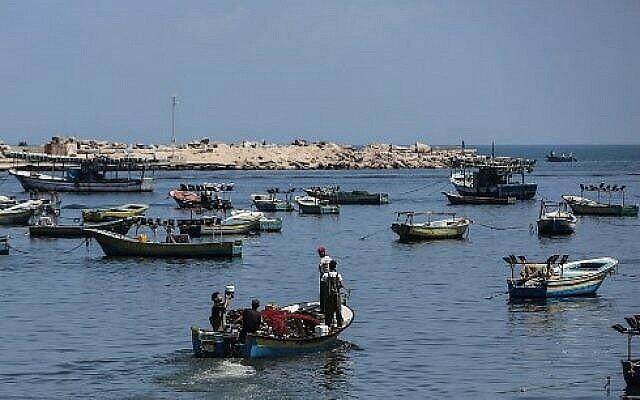 صيادون فلسطينيون في طريقهم الى البحر المتوسط في مدينة غزة، 18 يونيو، 2019. (Mahmud Hams / AFP)