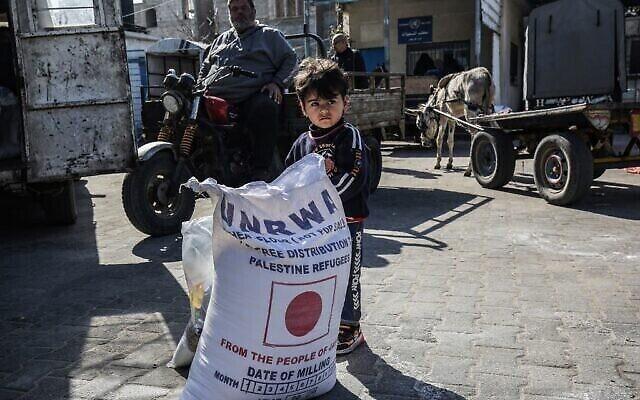 في هذه  الصورة التي تم التقاطها في 2 فبراير ، 2020، طفل يقف بجانب كيس دقيق بينما يأتي الناس لتلقي مساعدات غذائية من مركز توزيع تابع لوكالة الأمم المتحدة لإغاثة وتشغيل اللاجئين (الأونروا) في خان يونس بقطاع غزة . (SAID KHATIB / AFP)