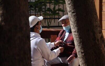 """الناجي من المحرقة موطي ليبر  (88 عاما)، يتلقى الرعاية من متطوع في مقر مؤسسة """"ياد عيزر لحافير"""" ، التي تدعم الناجين من المحرقة من خلال تزويدهم بالطعام بالإضافة إلى المساعدة الطبية والنفسية، في حيفا، 24 يناير، 2021, (Emmanuel DUNAND / AFP)"""