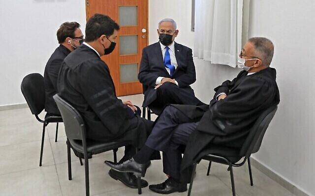 رئيس الوزراء بنيامين نتنياهو يجلس مع محاميه خلال جلسة استماع في محاكمته بالفساد في محكمة القدس المركزية، 5 أبريل 2021 (POOL / AFP)
