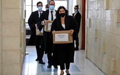 مدعو الدولة يحملون صناديق ملفات الى جلسة استماع في قضية فساد لرئيس الوزراء بنيامين نتنياهو في محكمة القدس المركزية، 5 أبريل 2021 (POOL / AFP)