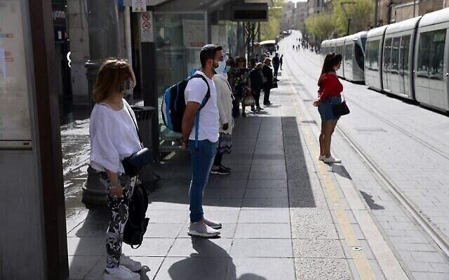 أشخاص يقفون دقيقتي صمت في القدس في 8 أبريل 2021 مع إطلاق صفارات الإنذار في جميع أنحاء إسرائيل لمدة دقيقتين بمناسبة اليوم السنوي لإحياء ذكرى ستة ملايين يهودي من ضحايا المحرقة النازية. (Menahem KAHANA / AFP)