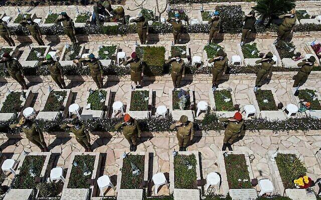 """التقطت هذه الصورة في 13 أبريل 2021 ، في """"يوم هزيكارون"""" (يوم الذكرى الإسرائيلي)، وتُظهر  مشهدا تم التقاطه من الجو لجنود إسرائيليين يؤدون التحية على القبور في مقبرة كريات شاؤول العسكرية في مدينة تل أبيب.  (JACK GUEZ / AFP)"""