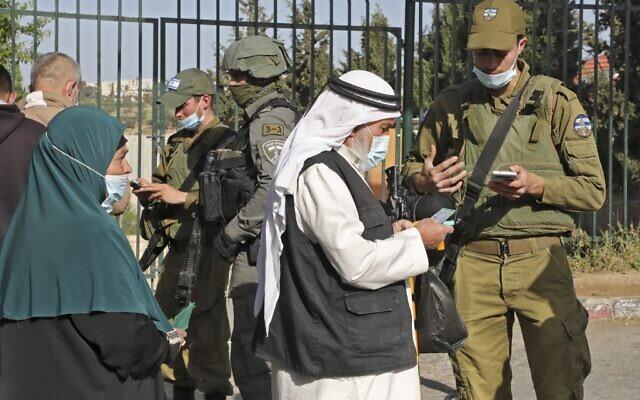 جنود إسرائيليون يتحققون من شهادات التطعيم ضد فيروس كورونا للفلسطينيين الذين يدخلون القدس لحضور صلاة الجمعة الأولى من شهر رمضان في المسجد الأقصى، عند حاجز بالقرب من بلدة بيت لحم بالضفة الغربية، 16 أبريل 2021 (Hazem BADER / AFP)