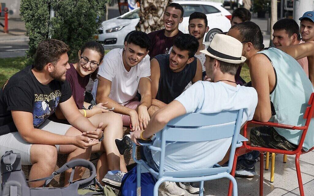 مجموعة من الشباب تجتمع في أحد شوارع مدينة تل أبيب الساحلية الإسرائيلية في 18 أبريل 2021، بعد أن أعلنت السلطات عن إلغاء فرض وضع الكمامات للوقاية من كوفيد -19 في الخارج. (JACK GUEZ / AFP)