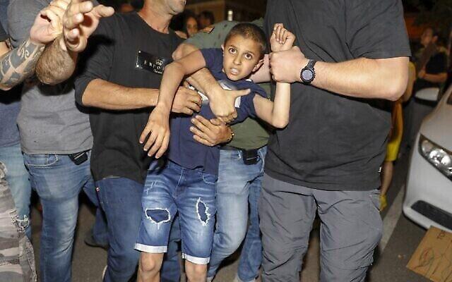 الشرطة الإسرائيلية تعتقل طفلا خلال مظاهرة لمواطنين عرب ونشطاء من اليسار ضد استيلاء مجموعات يمينية على منازل في يافا، بالقرب من تل أبيب، في 19 أبريل، 2021. (AHMAD GHARABLI / AFP)