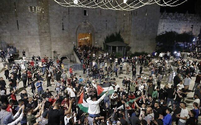 متظاهرون فلسطينيون يرفعون الأعلام الفلسطينية أثناء تجمعهم بالقرب من باب العامود في البلدة القديمة في القدس، 25 أبريل، 2021. (Ahmad GHARABLI / AFP)