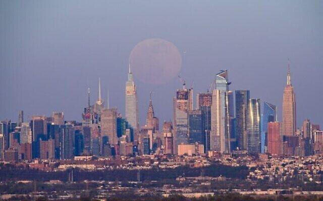 """بدر شهر أبريل، المسمى """"القمر الوردي الضخم""""، يظهر فوق أفق مانهاتن، 26 أبريل 2021 (Angela Weiss / AFP)"""