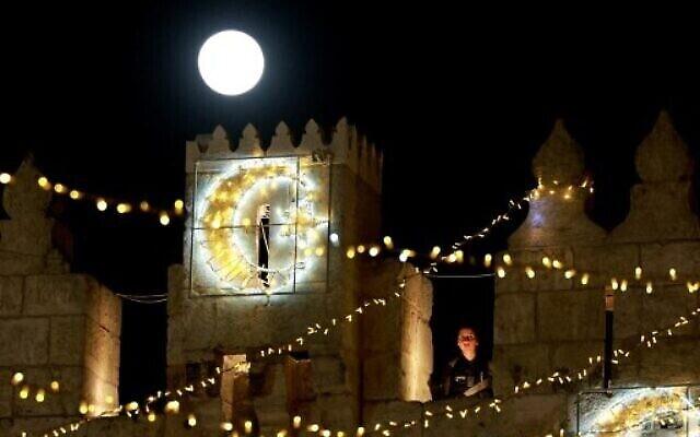 """بدر شهر أبريل، المسمى """"القمر الوردي الضخم""""، يظهر فوق باب العامود بينما تقوم الشرطة الإسرائيلية بالحراسة في البلدة القديمة في القدس، 27 أبريل 2021 (Menahem KAHANA / AFP)"""