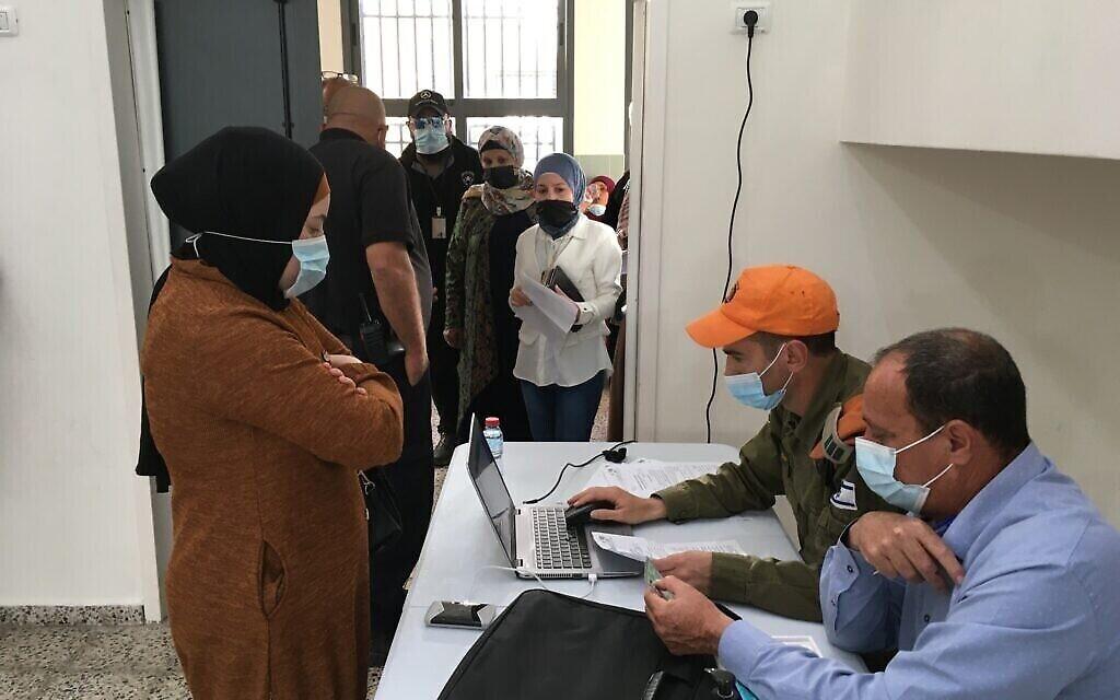 روعي وولف، الذي يعمل على الكمبيوتر، وهو رقيب في الجيش الإسرائيلي يستقبل متلقي التطعيم المحتملين بينما يقوم قيصر كبها، مدير المجلس الإقليمي بسمة، بفحص وثائق هويتهم. (Uriel Heilman/ JTA)