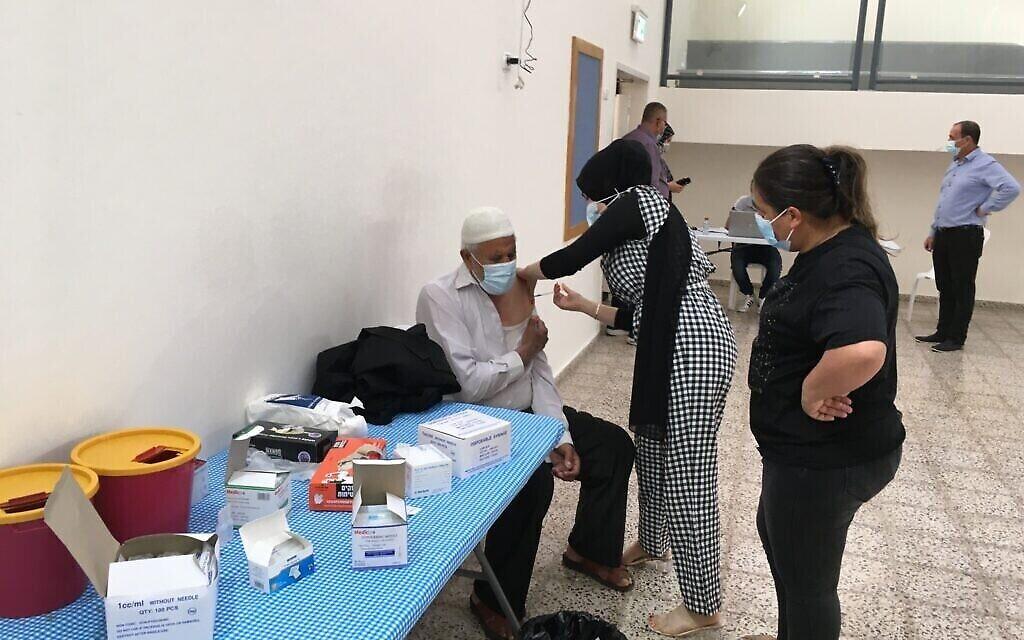 رجل يتلقى جرعته الثانية من اللقاح في محطة تطعيم مؤقتة في برطعة ، إسرائيل. (Uriel Heilman/ JTA)