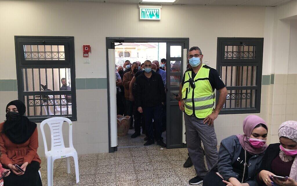 في محطة تطعيم ضد فيروس كورونا في بلدة برطعة العربية الإسرائيلية، ينتظر الفلسطينيون إلى جانب المواطنين الإسرائيليين على أمل الحصول على جرعة من جرعات اللقاح غير الكافية، 8 أبريل، 2021. (Uriel Heilman / JTA)