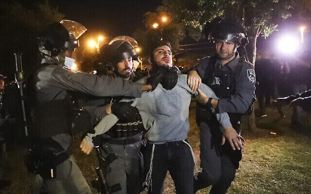 """عناصر شرطة الحدود الإسرائيلية يعتقلون شابًا إسرائيليًا عضوًا في """"لهافا""""، وهي جماعة يهودية متطرفة، أثناء محاولة ناشطو الحركة الاقتراب من باب العامود للاحتجاج وسط توترات متصاعدة في المدينة، خارج البلدة القديمة في القدس، 22 أبريل 2021 (AP Photo / Ariel Schalit)"""