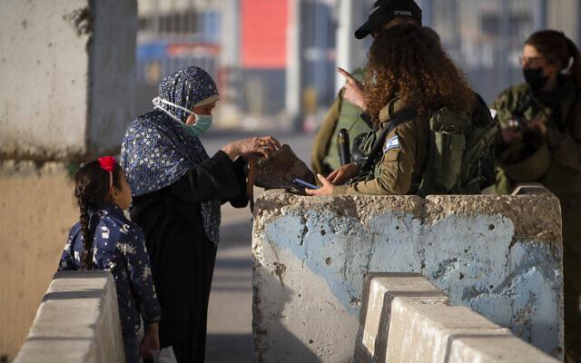جنود إسرائيليون يفحصون سيدة فلسطينية أثناء انتظارها لعبور حاجز قلنديا بين مدينة رام الله بالضفة الغربية والقدس، 23 أبريل 2021 (AP Photo/Majdi Mohammed)